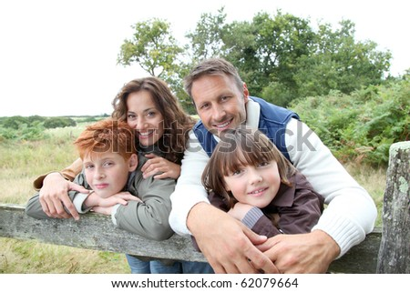 Family leaning on a fence - stock photo