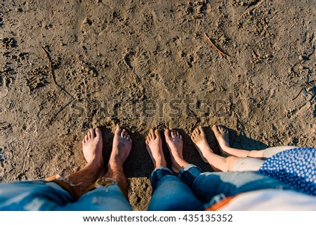 Family legs standing on the beach - stock photo