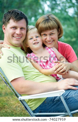 family lifestyle portrait of a mum and dad with their children sitting on folding chair  in the green  park - stock photo
