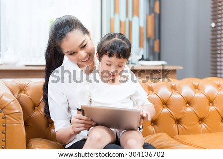 Family looking at a laptop lying down  - stock photo