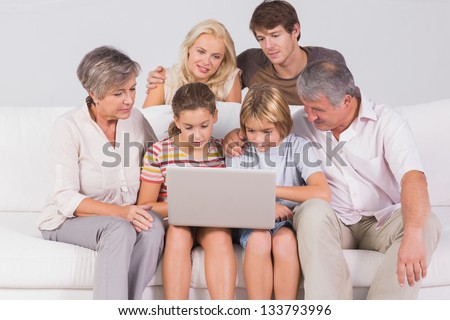 Family looking at laptop on couch in sitting room - stock photo