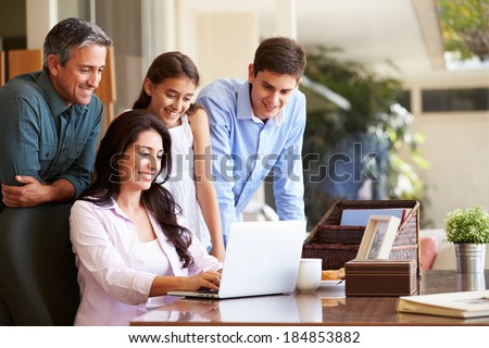 Family Looking At Laptop Together - stock photo
