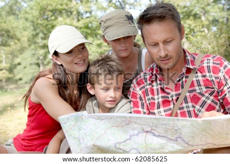 Family looking at map on a hiking day - stock photo