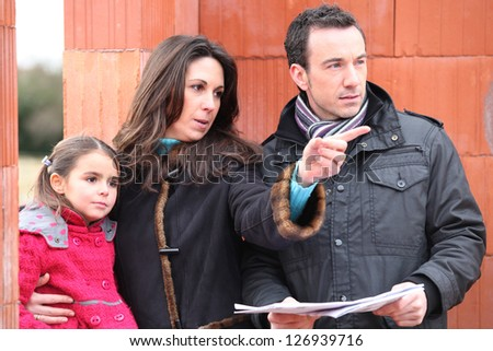 family looking at the plan of their future house - stock photo