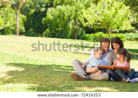 Family looking at their photo album in the park - stock photo