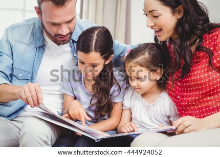 Family looking in picture book while sitting on sofa at home