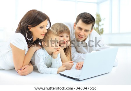 family looking into the laptop enthusiastically - stock photo