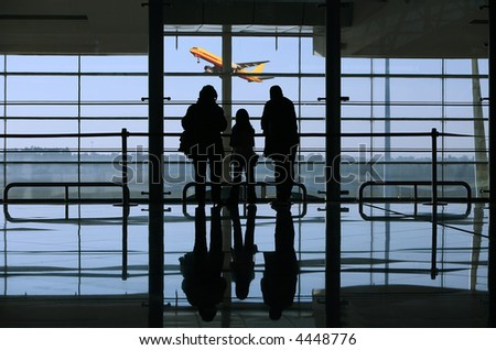 family looking to a airplane through the window in the airport - stock photo