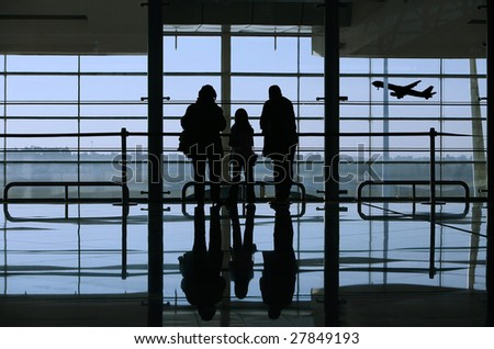 family looking to an airplane through the window in the airport - stock photo