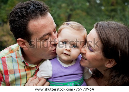 Family love - parents kiss for cute little daughter - stock photo