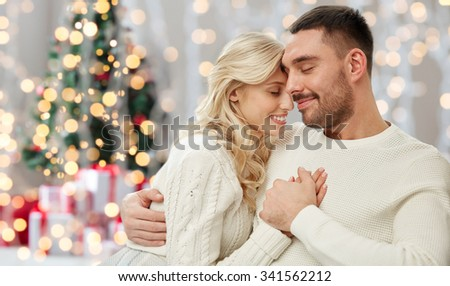 family, love, winter, holidays and people concept - happy couple over christmas tree lights background - stock photo