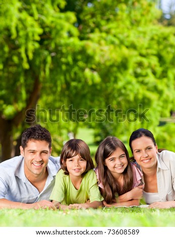 Family lying down in the park - stock photo