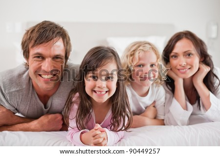 Family lying in a bed together - stock photo