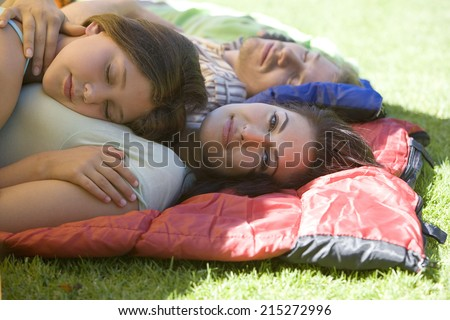 Family lying on sleeping bags in tent entrance on garden lawn, girl sleeping on mother�¢â�¬â�¢s chest, woman smiling, side view, portrait - stock photo