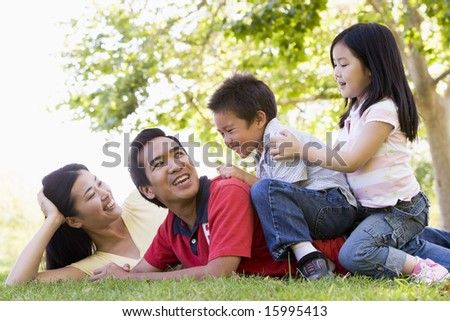 Family lying outdoors being playful and smiling - stock photo