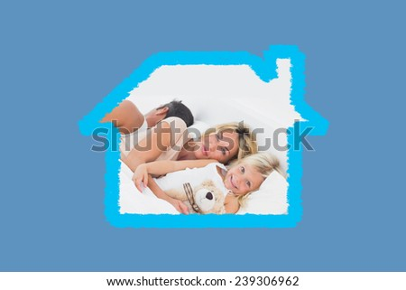 Family lying together on a bed against blue background with vignette - stock photo