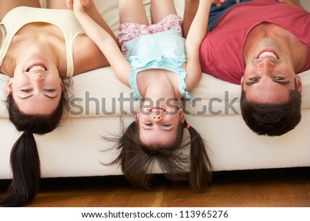 Family Lying Upside Down On Sofa With Daughter - stock photo