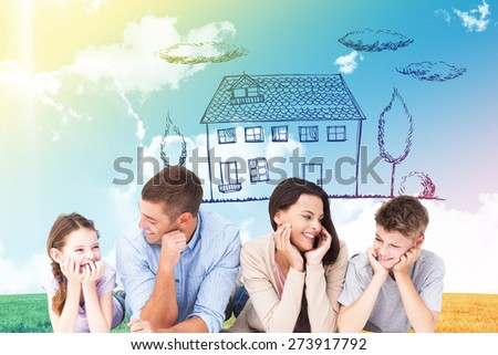 Family lying with head in hands against blue sky over green field - stock photo