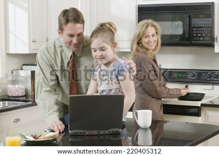 Family making breakfast and looking at laptop - stock photo