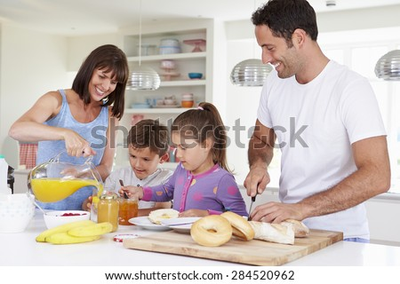 Family Making Breakfast In Kitchen Together - stock photo