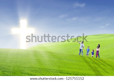 Family members are walking happily towards bright cross in the park - stock photo