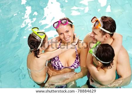 Family members looking at cheerful woman who smiling at camera - stock photo