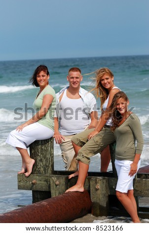 Family members, 3 sisters and 1 brother, together on jetty in surf