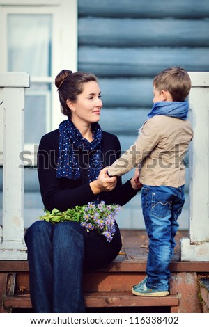 Family. Mom and son near a country house. - stock photo
