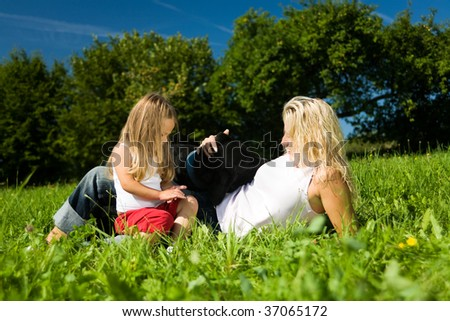 Family (mother and daughter) on a sunlit meadow with their dog