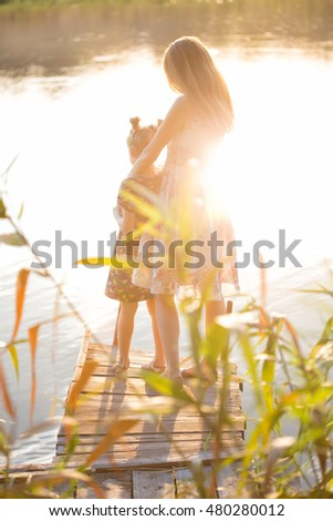 family - mother and daughter standing on the pier in sunset light