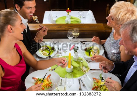 Family, mother and father with adult children and daughter or son in law �¢??fine dining in nice restaurant or hotel - stock photo
