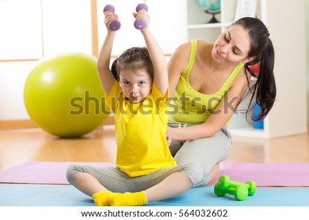family mother and kid daughter are engaged in fitness, yoga, exercise at home
