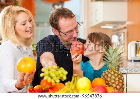 Family - mother, father and child - with lots of fruits for breakfast food, this is healthy nutrition - stock photo