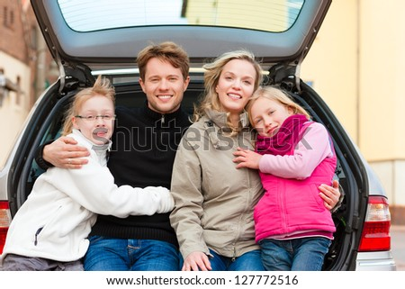 Family, mother, father and children, sitting in the trunk, they make a trip