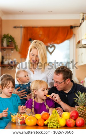 Family (mother, father and children) with lots of fruits, this is healthy nutrition for breakfast food - stock photo