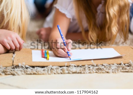 Family, mother, father and daughters are at home, the children coloring on the floor, cropped image