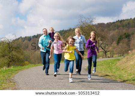 Family (mother, father and four children) is running outdoors in spring - stock photo