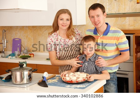 Family - mother,father and 7 year old son  are cooking pizza together - stock photo