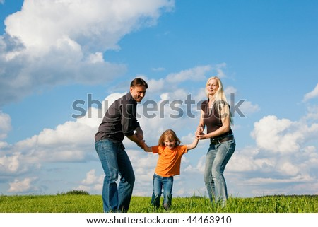 Family - mother, father, child - running over the grass of a green meadow at a late summer afternoon - stock photo