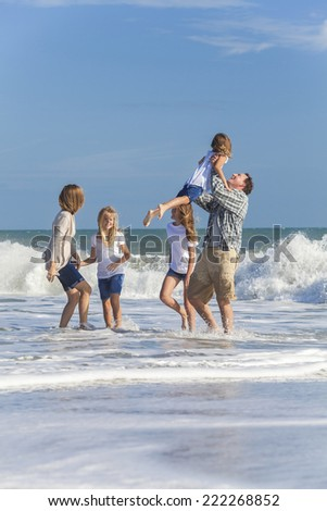 Family mother, father, daughters, parents and female girl children on vacation playing in the sea on a beach