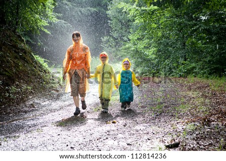 Family, mother, son and daughter, out walking along a track through the woods in the rain. - stock photo