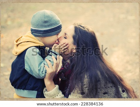 family mother with child son in park are playing  - stock photo