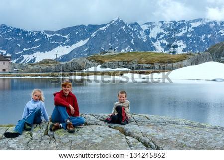 Family (mother with children) near summer Alps mountain lake (Switzerland, Passo del San Gottardo, Lago della Piazza) - stock photo