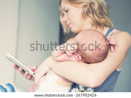 Family mother with newborn baby infant child home watching telephone  - stock photo