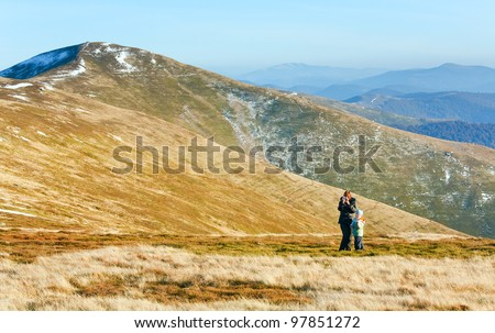 Family (mother with son) walk and make photo on autumn  mountain plateau - stock photo