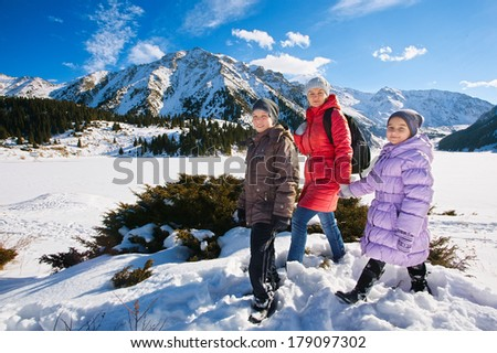 Family (mother with two children) take a walk on winter mountain slope (Big Almaty Lake, Kazakhstan) - stock photo