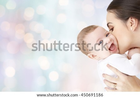 family, motherhood, parenting, people and child care concept - happy mother kissing adorable baby over blue holidays lights background