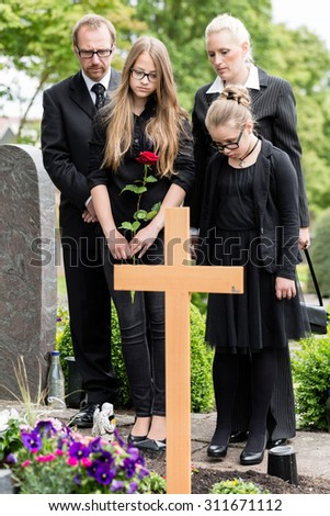 Family mourning at grave on graveyard or cemetery - stock photo
