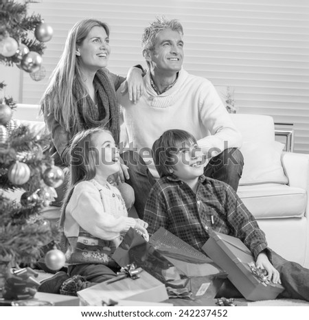Family near Chrismas tree awaiting Santa Claus arrival.