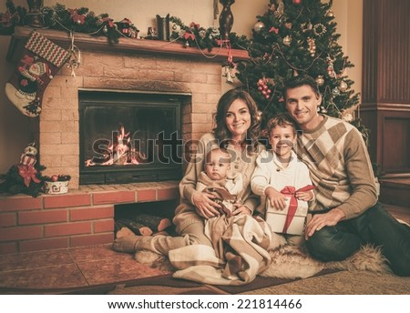 Family near fireplace in Christmas decorated house interior with gift box